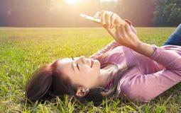 Teléfono celular conmovedor sonriente de la mujer joven y mentira en prado Imagenes de archivo