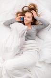 Teléfono celular de cama de la muchacha del adolescente Imagen de archivo