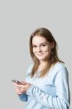 Teléfono celular de explotación agrícola de la muchacha Foto de archivo