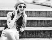 Teléfono celular de la muchacha del inconformista que habla mientras que se sienta en las escaleras Foto de archivo