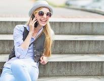 Teléfono celular de la muchacha feliz del inconformista que habla mientras que se sienta en las escaleras Fotografía de archivo libre de regalías