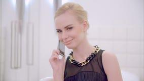 Teléfono celular de la muchacha que habla rubia joven almacen de metraje de vídeo
