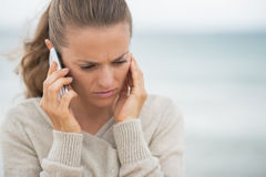Teléfono celular de la mujer que habla en cuestión en la playa Imágenes de archivo libres de regalías