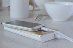Teléfono celular de los gastos bancarios del poder en la tabla de cocina fotografía de archivo libre de regalías