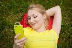 Teléfono celular de tenencia de la muchacha y música que escucha con el auricular blanco Foto de archivo