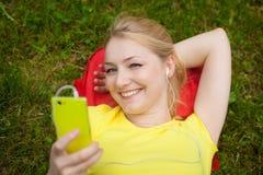 Teléfono celular de tenencia de la muchacha y música que escucha con el auricular blanco Fotos de archivo