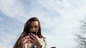Teléfono celular de tenencia de la mujer en parque almacen de video