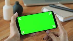 Teléfono celular de tenencia de la persona con la pantalla de visualización verde a disposición almacen de metraje de vídeo