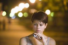 Teléfono celular de tenencia del adolescente en la calle Foto de archivo libre de regalías