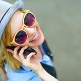 Teléfono celular del inconformista que habla joven feliz en stree de la ciudad Fotos de archivo libres de regalías