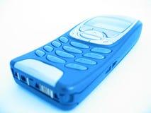 Teléfono celular en brillo azul foto de archivo