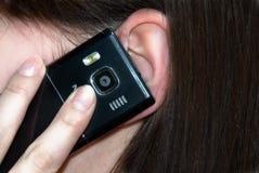 Teléfono celular en el oído de la muchacha Fotografía de archivo