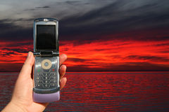 Teléfono celular en la puesta del sol Fotos de archivo