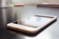 Teléfono celular en oficina de la tabla fotos de archivo