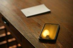 Teléfono celular en un escritorio Foto de archivo libre de regalías