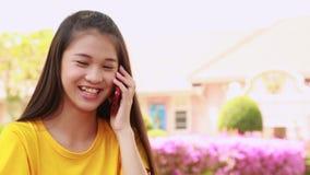Teléfono celular feliz de la mujer joven en el parque almacen de video