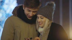 Teléfono celular feliz joven de la visión de los pares en una ciudad durante tiempo de la Navidad del invierno Comparta las memor almacen de video