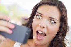 Teléfono celular joven chocado de la lectura de la hembra adulta Outd Fotos de archivo libres de regalías