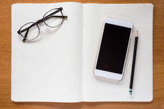 Teléfono celular, lentes, y lápiz en el cuaderno blanco Fotos de archivo