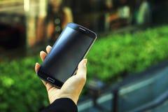 Teléfono celular, mano joven de la mujer de negocios que sostiene el teléfono elegante Fotos de archivo libres de regalías