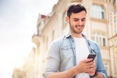 Teléfono celular positivo de tenencia del hombre fotografía de archivo libre de regalías