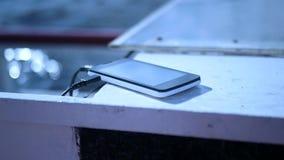 Teléfono celular que encarga cerca del agua, de la falta de definición y de los puntos culminantes HD, 1920x1080 almacen de metraje de vídeo