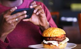 Teléfono celular que fotografía una hamburguesa Hamburguesa en la tabla del café Imagenes de archivo