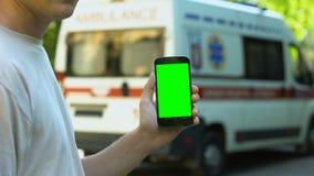Teléfono celular que se sostiene masculino, ambulancia en el fondo, uso para la llamada de emergencia metrajes
