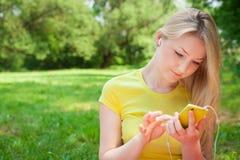 Teléfono celular rubio de tenencia de la muchacha y música que escucha con el headphon Fotografía de archivo
