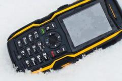 Teléfono celular rugoso en nieve Fotografía de archivo libre de regalías