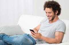 Teléfono celular sonriente de la explotación agrícola del hombre joven fotografía de archivo