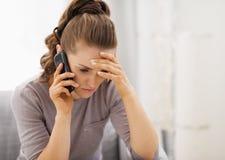 Teléfono celular subrayado de la mujer que habla joven Imagenes de archivo