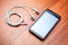 Teléfono celular y auricular negros imagenes de archivo