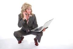 Teléfono celular y computadora portátil que hacen juegos malabares 2 de la mujer de negocios Imágenes de archivo libres de regalías