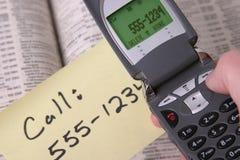 Teléfono celular y listín y nota de teléfonos Imagen de archivo libre de regalías
