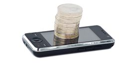 Teléfono celular y pila de monedas Imágenes de archivo libres de regalías