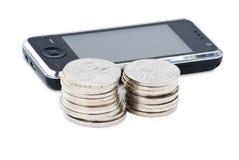 Teléfono celular y pilas de monedas Imagen de archivo