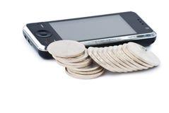 Teléfono celular y pilas de monedas Imágenes de archivo libres de regalías