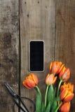 Teléfono celular y tulipanes Imagenes de archivo