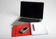 Teléfono, computadora portátil y cuaderno vacío Foto de archivo libre de regalías