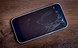 Teléfono con el vidrio quebrado en un background_ de madera oscuro imágenes de archivo libres de regalías