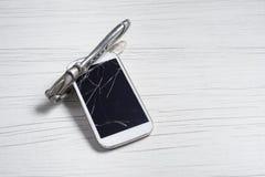 Teléfono con el vidrio quebrado y los cortadores de la nuez imágenes de archivo libres de regalías