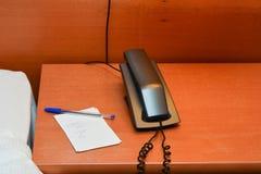 Teléfono con la nota sobre el escritorio Fotos de archivo