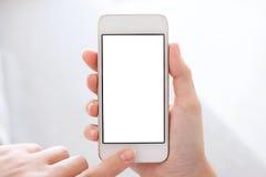 Teléfono con la pantalla aislada en manos femeninas Fotos de archivo