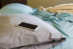 Teléfono de Android con una pantalla en blanco que pone en una almohada en una cama Fotografía de archivo