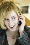 Teléfono de contestación de la mujer caucásica rubia joven Foto de archivo