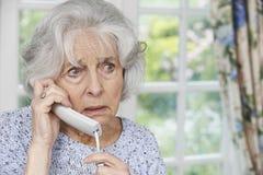 Teléfono de contestación de la mujer mayor preocupante en casa Imagenes de archivo