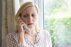 Teléfono de contestación de la mujer preocupante en casa fotografía de archivo libre de regalías