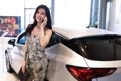 Teléfono de discurso de la morena admirable y el possing cerca de su nuevo coche en la sala de exposición de la representación imagen de archivo