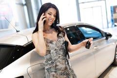 Teléfono de discurso de la morena admirable y el possing cerca de su nuevo coche en la sala de exposición de la representación fotos de archivo libres de regalías